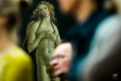 People stand in front of the 'Venus' by Italian painter Sandro Botticelli during a news conference about the planned exhibition 'The Botticelli Renaissance' in Berlin, Thursday, Jan. 15, 2015. The exhibition at Gemaeldegalerie (Gallery of Old Masters) in partnership with London's Victoria and Albert Museum will present masterpieces of Bottocelli from museums and collections around the world and also modern-day interpretations of his work by artists such as Edgar Degas, Rene Margritte, Andy Warhol and Cindy Sherman. The exhibition takes place from Sept. 24, 2015 until Jan. 24, 2016. (AP Photo/Markus Schreiber)