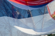 A Kosovo Serb man hangs in a tree waving a Serbian flag during the visit of Serbian prime minister Aleksandar Vucic in the Kosovo village of Gracanica on Wednesday, Jan. 14, 2015. Serbia's prime minister is making a landmark visit to Kosovo on Wednesday, signifying the first step towards normalizing relations between the two countries. (AP Photo/Visar Kryeziu)
