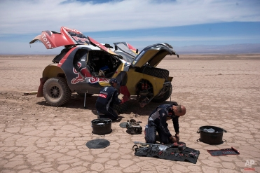 Peugeot driver Stephane Peterhansel and co-pilot Jean Paul Cottret, both of France, work to fix their car after a mechanical problem during the ninth stage of the Dakar Rally 2015 between the cities of Iquique and Calama, Chile, Tuesday, Jan. 13, 2015. The race will finish on Jan. 17, passing through Bolivia and Chile before returning to Argentina where it started. (AP Photo/Felipe Dana)