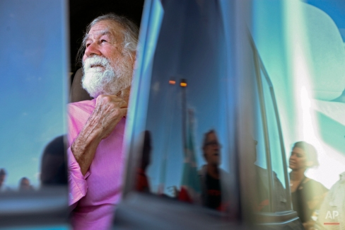 Norberto Gonzalez Claudio, who completed a prison sentence for his role in a 1983 holdup in Connecticut carried out by Puerto Rican militants, looks out at supporters after arriving at the international airport in Carolina, Puerto Rico, Thursday, Jan. 15, 2015. The 69-year-old Puerto Rican arrived Thursday in the U.S. territory just hours after he was released from a prison in central Florida. Supporters greeted Gonzalez with raised fists in the air and waved Puerto Rican flags. (AP Photo/Gerardo Bello)