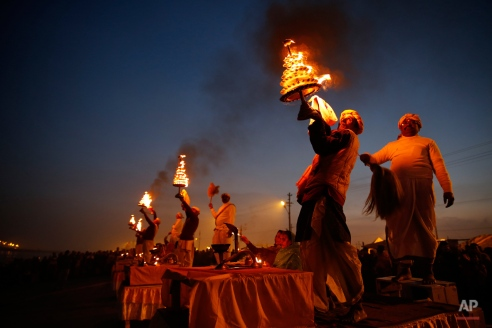 Indian Hindu priest rotates a traditional oil lamp in circular movements as he performs evening rituals at Sangam, the confluence of rivers Ganges and Yamuna, during the annual month long Hindu religious fair 'Magh Mela' in Allahabad, India, Monday, Jan. 20, 2014. (AP Photo/Rajesh Kumar Singh)