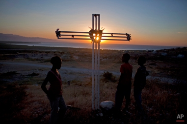 In this picture taken Jan. 8, 2013, a cross memorializing the victims of the 2010 earthquake who are buried at the spot in mass graves is silhouetted against the setting sun in Titanyen, north of Port-au-Prince, Haiti. (AP Photo/Dieu Nalio Chery)