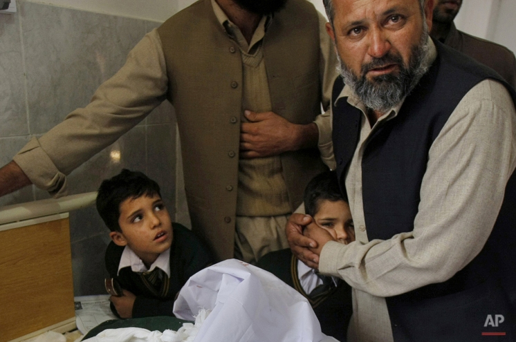 A Pakistani man comforts a student standing at the bedside of a boy who was injured in a Taliban attack at a local hospital in Peshawar, Pakistan, Tuesday, Dec. 16, 2014. (AP Photo/Mohammad Sajjad)