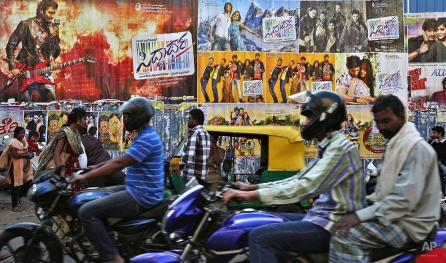 Vehicles move near a wall occupied with regional language movie posters at a busy shopping district in Bangalore, India, Friday, Jan. 23, 2015. (AP Photo/Aijaz Rahi)