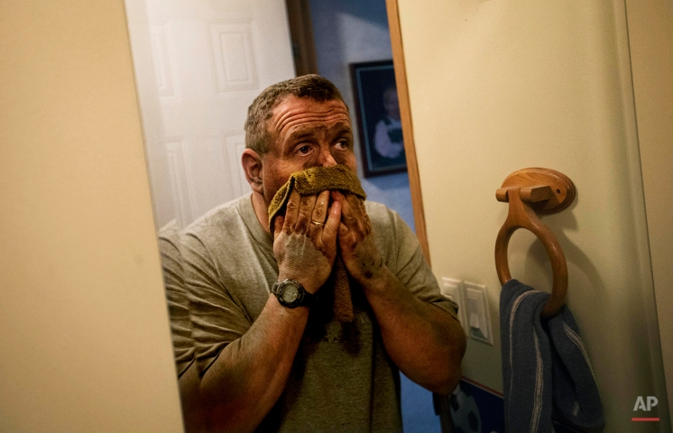 """In this Oct. 20, 2014 photo, third generation coal miner Keith Johnson washes coal dust off his face in his bathroom as he arrives home after working the graveyard shift underground in a coal mine in Evarts, Ky. Johnson, 43, is paying on a $20,000 hospital bill incurred while working at a company that offered no insurance. He's spent about $40,000 from his retirement fund to stay in Harlan. """"A few years ago, I would have said we had it made and we was going to live a long life and retire here. But it's dim right now,"""" says Johnson. """"There's no jobs, and what jobs are there are dwindling out. It's a bleak outlook for sure for the coalfields in eastern Kentucky."""" (AP Photo/David Goldman)"""