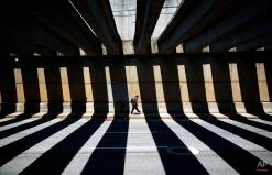A pedestrian walks through a downtown underpass as the midday sun casts shadows from overhead beams, Thursday, Aug. 7, 2014, in Atlanta. (AP Photo/David Goldman)