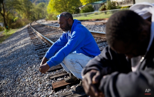 """In this Oct. 19, 2014 photo, unemployed coal miner Steven Fields, 50, left, sits on the railroad tracks near his home in Coxton, Ky. Fields was laid off from his coal mining job five years ago and plans to leave his family behind to look for work in Alabama. """"There just ain't nothing for me to do here,"""" says Fields. """"I figured I got about ten years left to work, I'm fighting for those ten years."""" (AP Photo/David Goldman)"""