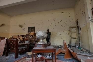 A Pakistani photographer takes pictures in principal's room at the Army Public School attacked the day before by Taliban gunmen, in Peshawar, Pakistan, Wednesday, Dec. 17, 2014. (AP Photo/Mohammad Sajjad)