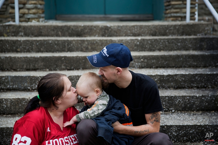 """In this Oct. 16, 2014 photo, unemployed coal miner Jeremy Adams, 26, right, sits with his 15-month-old son Christopher and wife Tiffany Cox, 26, as they wait for a school bus to drop off Cox's two daughters from school in Lynch, Ky. """"It's depressing. Nobody can find a job around here,"""" says Adams who was laid off from his mining job three years ago. (AP Photo/David Goldman)"""