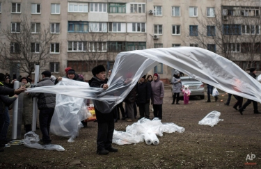 Local residents prepare plastic sheeting to cover broken windows near heating tents after Saturday's shelling at Vostochniy district of Mariupol, Ukraine, Monday, Jan. 26, 2015. At least 5,100 people have been killed in eastern Ukraine since fighting began in April 2014, but violence this week was the most intense since a cease-fire deal was signed in September. (AP Photo/Evgeniy Maloletka)