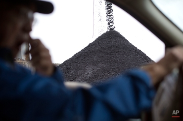 In this Oct. 15, 2014 photo, coal comes off a conveyer belt as mine owner C.V. Bennett III drives by at the Perkins Branch Coal Mine in Cumberland, Ky. These days, the family's mines are even having a hard time moving what coal they can produce. It seems everything from South Dakota shale oil to Iowa corn takes precedence when it comes to rail cars and locomotives. (AP Photo/David Goldman)