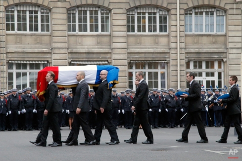 French police officers carry the coffin of Police officer Franck Brinsolaro, killed at Charlie Hebdo during a ceremony to pay tribute to the three police officers killed in the attacks, in Paris, France, Tuesday, Jan. 13, 2015. Police officers Ahmed Merabet, 40, Franck Brinsolaro, 49, were killed during the attacks at Charlie Hebdo, and Clarissa Jean-Philippe killed in Montrouge last week. (AP Photo/Francois Mori)