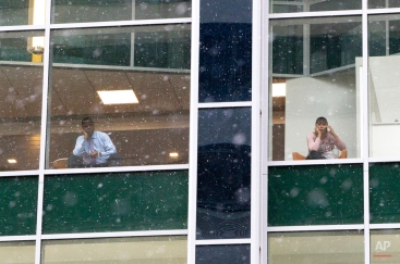 People look out from office building windows as snow falls in downtown Philadelphia, Monday, Jan. 26, 2015. The Philadelphia-to-Boston corridor of more than 35 million people began shutting down and bundling up against a potentially history-making storm that could unload a paralyzing amount of snow. (AP Photo/Michael R. Sisak)