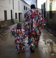 Sergio Salgado, 31-years-old, and a boy walk the streets dressed as Jarramplas during the Jarramplas Festival in Piornal, Spain, Monday, Jan. 20, 2014. (AP Photo/Andres Kudacki)