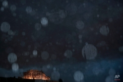 The ancient Parthenon temple is illuminated as raindrops fall during a storm in Athens, Monday, Jan. 26, 2015. Greece's radical left Syriza party gained the key backing needed to form a government Monday, creating a surprise alliance with a small right-wing party that signals possible confrontation over the country's bailout. (AP Photo/Petros Giannakouris)