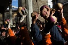People hold turnips to throw at Jarramplas during the Jarramplas Festival in Piornal, Spain, Monday, Jan. 20, 2014. (AP Photo/Andres Kudacki)