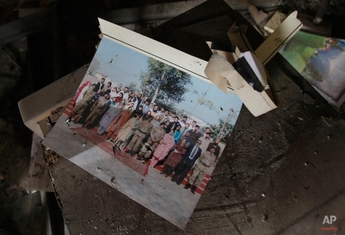 A group photograph of students of the Army Public School that was attacked the day before by Taliban gunmen, is seen in the school principal's office in Peshawar, Pakistan, Wednesday, Dec. 17, 2014. (AP Photo/Mohammad Sajjad)
