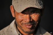 A Nepalese laborer smiles as he takes a break during work at a cement lined pipe factory on the outskirts of Kathmandu, Nepal, Monday, Jan. 12, 2015. Laborers usually work from 9 a.m. to 5 p.m. everyday earning $105 per month. (AP Photo/Niranjan Shrestha)