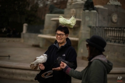 A tourist, left, grimaces as a street entertainer places her doves on him for his friend to photograph, in Madrid, Spain, Friday, Jan. 2, 2015. (AP Photo/Andres Kudacki)