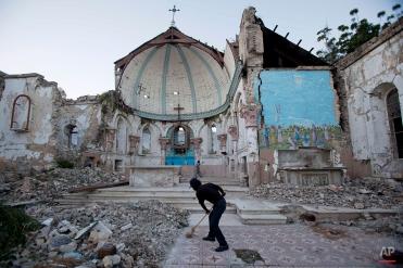 A man sweeps an exposed tiled area of the earthquake-damaged Santa Ana Catholic church, where he now lives, in Port-au-Prince, Haiti, Saturday, Jan. 12, 2013. (AP Photo/Dieu Nalio Chery)