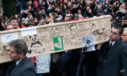 Pallbearers carry the casket of Charlie Hebdo cartoonist Bernard Verlhac, known as Tignous, decorated by friends and colleagues of the satirical newspaper Charlie Hebdo, at the city hall of Montreuil, outside east of Paris, Thursday, Jan. 15, 2015. Funerals are being held today for at least of the six staff members of the satirical newspaper Charlie Hebdo, who were killed last week in a terror attack on their offices in Paris. (AP Photo/Michel Euler)