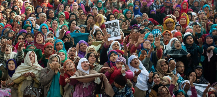 A Kashmiri Muslim woman holds up medical reports, with the belief that ailments will be healed, as devotees raise their hands towards a relic, believed to be a hair from the beard of Islam's Prophet Muhammad, being displayed by a priest at the Hazratbal shrine on the Friday following Eid-e- Milad, marking the birth anniversary of the Prophet, in Srinagar, India, Friday, Jan. 9, 2015. (AP Photo/Dar Yasin)