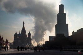 Steam rises from a power plant behind the Moskva River as tourists walk along the Red Square with St. Basil's Cathedral, at left, in Moscow, Russia, Thursday, Jan. 22, 2014. The structure at right is the Spassky Tower, which is currently being renovated. (AP Photo/ Alexander Zemlianichenko)