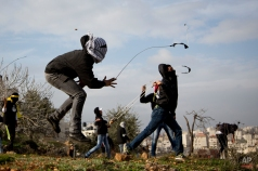 A masked Palestinian man uses a slingshot during clashes with Israeli soldiers outside the Ofer military prison near the West Bank city of Ramallah on Friday, Jan. 2, 2015. (AP Photo/Majdi Mohammed)