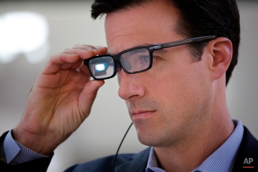 Chris Barnes tries out Toshiba Glass at the Toshiba booth at the International CES Wednesday, Jan. 7, 2015, in Las Vegas. (AP Photo/Jae C. Hong)