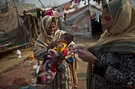 A child carried by her mother cries after being vaccinated against polio by health worker in a slum that hosts Christian families on the outskirts of Islamabad, Pakistan, Tuesday, Jan. 20, 2015. (AP Photo/Muhammed Muheisen)