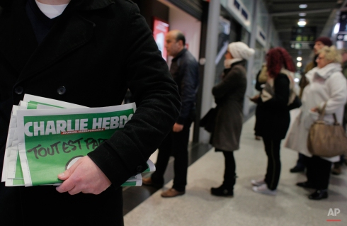 A man leaves after buying Charlie Hebdo newspapers as people queue at a newsstand in Paris, Wednesday, Jan. 14, 2015. In an emotional act of defiance, Charlie Hebdo resurrected its irreverent and often provocative newspaper, featuring a caricature of the Prophet Muhammad on the cover that drew immediate criticism and threats of more violence. (AP Photo/Christophe Ena)