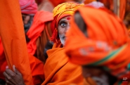 An Indian Sadhu, or Hindu holy man, sits for a community feast at the Sangam, the confluence of the Rivers Ganges, Yamuna and mythical Saraswati, during the annual month-long Magh Mela religious fair in Allahabad, India, Friday, Jan. 16, 2015. Hundreds of thousands of devout Hindus are expected to take holy dips at the confluence during the astronomically auspicious period of over 45 days celebrated as Magh Mela. (AP Photo/Rajesh Kumar Singh)