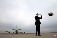 Marine Cpl. Chaz Sorensen loses his hat due to the jet's exhaust as Air Force One, with President Barack Obama aboard, departs from Andrews Air Force Base, Md., Wednesday, Jan. 21, 2015, en route to Boise State University where he will discuss the themes in his State of the Union address. (AP Photo/Jose Luis Magana)