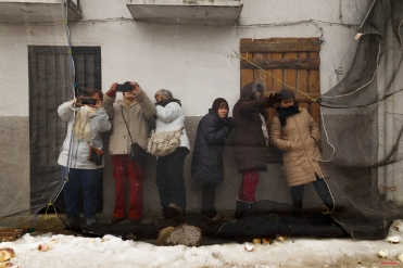 People gather under a net to prevent getting hit while others throw turnips at the Jarramplas as he makes his way through the streets beating his drum during the Jarramplas Festival in Piornal, Spain, Tuesday, Jan. 20, 2015. AP Photo/Daniel Ochoa de Olza)