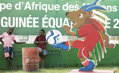 Unidentified men stand outside a ticketing office ahead of the opening African Cup of Nations Group A soccer match in Bata, Equatorial Guinea, Friday Jan. 16, 2015. (AP Photo/Themba Hadebe)