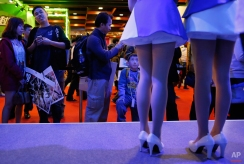 A young boy watches hostesses as he waits to play a new video game at the Taipei Game Show in Taipei, Taiwan, Wednesday, Jan. 28, 2015. The game show, one of the leading digital interactive gaming events in Asia, will run from Jan. 28 through Feb. 1. (AP Photo/Wally Santana)