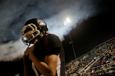 """In this Oct. 17, 2014 photo, spectators watch from the stands during a Harlan County High School football game in Harlan, Ky. As the Harlan County High Black Bears stormed the field, a cannon boomed and a loudspeaker blasted the chorus of Darrell Scott's ballad, """"You'll Never Leave Harlan Alive!"""" It's Friday night, but the stands at Coal Miners' Memorial Stadium are barely a third full. (AP Photo/David Goldman)"""