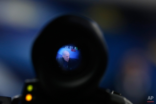 Greece's new Finance Minister Yanis Varoufakis is seen through a camera viewfinder as he makes statements during a handover ceremony at the Finance Ministry in Athens, Wednesday, Jan. 28, 2015. Greece's new leftist prime minister Alexis Tsipras says his government's top priorities are to negotiate with Greece's partners to resolve the country's financial predicament and to deal with what he describes as Greece's humanitarian crisis. (AP Photo/Petros Giannakouris)