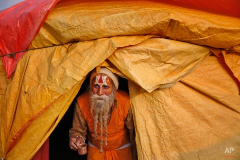 """An Indian Hindu Holy man carries a glass as he walks out of his tent to perform a ritual ahead of the annual month long Hindu religious fair """"Magh Mela"""" in Allahabad, India, Sunday, Jan. 4, 2015. Hundreds of thousands of devout Hindus camp and take a bath at the confluence during the astronomically auspicious period of over 45 days that begins on Jan. 5, hoping to rid themselves of their sins and attain prosperity. (AP Photo/Rajesh Kumar Singh)"""