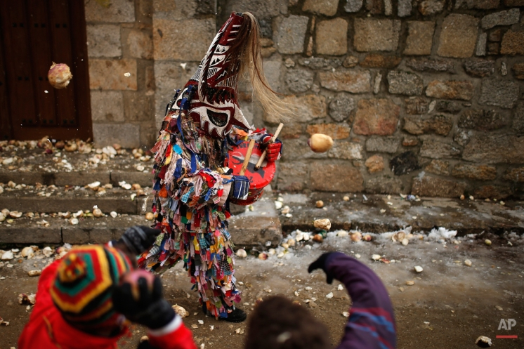 People throw turnips at the Jarramplas as he makes his way through the streets beating his drum during the Jarramplas Festival in Piornal, Spain, Monday, Jan. 20, 2014. (AP Photo/Andres Kudacki)