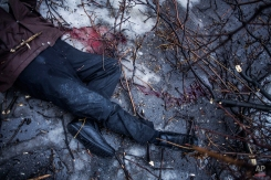 The remains of a man lie near a bus stop that was damaged in shelling by the Ukrainian army in Donetsk, eastern Ukraine, Tuesday, Jan. 20, 2015. At least three civilians were killed in shelling Tuesday in eastern Ukraine as fighting continued between government and rebel forces in the separatist-held city of Donetsk. (AP Photo/Manu Brabo)