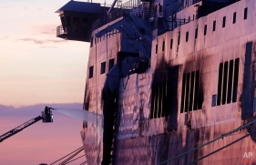 A firefighter sprays water on the Norman Atlantic ferry after it was towed into the port of Brindisi, southern Italy, Saturday, Jan. 3, 2015. (AP Photo/Antonio Calanni)