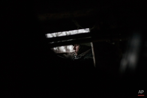 A Russian backed separatist rebel watches his position at the gate of a shelter under shelling in the Kievsky district, 3 km from the Airport, in Donetsk, Ukraine, Thursday, Jan. 22, 2015. A mortar shell hit a bus in the eastern Ukrainian rebel stronghold of Donetsk on Thursday, killing at least 13 people, the separatist leader in the city said. It was unclear immediately which side was responsible for the attack, which killed passengers instantly and blew out the windows of a nearby building. (AP Photo/Manu Brabo)