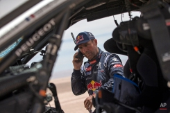 Peugeot driver Stephane Peterhansel, from France, talks on a sat phone after a mechanical problem during the ninth stage of the Dakar Rally between the cities of Iquique and Calama, Chile, Tuesday, Jan. 13, 2015. The race will finish on Jan. 17, passing through Bolivia and Chile before returning to Argentina where it started. (AP Photo/Felipe Dana
