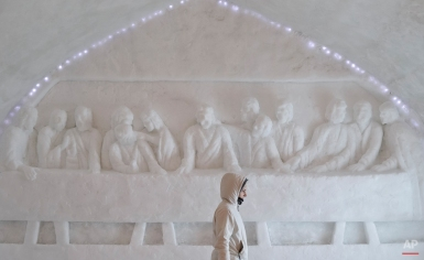 A woman walks by a depiction of the Last Supper cut in frozen snow inside a church built entirely from ice blocks cut from a frozen lake before a blessing religious service at the Balea Lac resort in the Fagaras mountains, Romania, Thursday, Jan. 29, 2015. The blessing was performed jointly by priests from all Christian denominations in Romania and the church, built at an altitude of over 2,000 meters, will host all types of religious events like weddings and baptizing ceremonies as long as the cold weather lasts. (AP Photo/Vadim Ghirda)