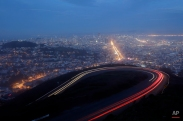 Cars make their way up a windy road on Twin Peaks as the sun sits over the bay on Friday, Jan. 9, 2015, in San Francisco. (AP Photo/Marcio Jose Sanchez)