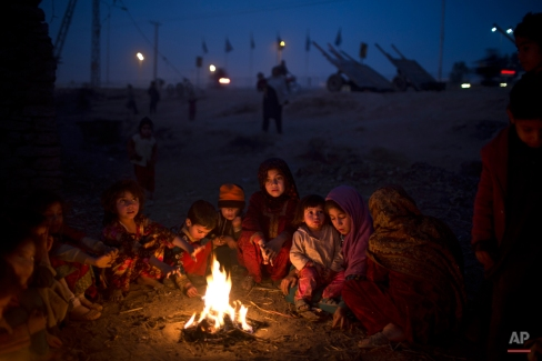 Afghan refugees and internally displaced Pakistani children from tribal areas gather around a fire to warm themselves near their mud homes in a slum on the outskirts of Islamabad, Pakistan, Tuesday, Jan. 6, 2015. (AP Photo/Muhammed Muheisen)