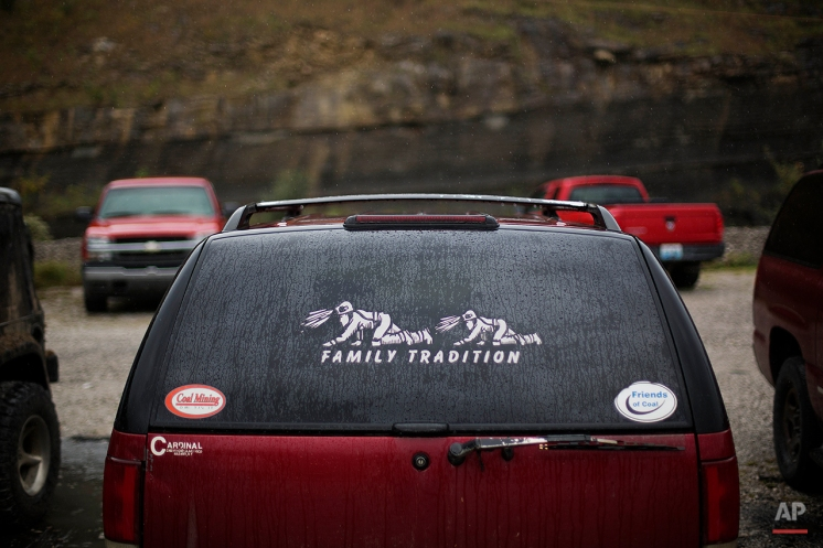 In this Oct. 15, 2014 photo, a sticker is fixed to a rear view window on a coal miner's car at the Perkins Branch coal mine in Cumberland, Ky. Since 1980, the county has lost nearly half of its under-35 population. (AP Photo/David Goldman)