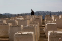 An ultra-Orthodox Jewish man walks in a cemetery during the funeral of four French Jewish victims of the attack last week on a kosher grocery store in Paris, in Jerusalem, Tuesday, Jan. 13, 2015. Thousands of mourners joined Israeli leaders and the families of Yoav Hattab, Yohan Cohen, Francois-Michel Saada and Phillipe Braham, four Jewish victims of the Paris terror attack, for an emotional funeral procession on Tuesday, reflecting the deep sense of connection and concern in Israel over the safety of fellow Jews in Europe. (AP Photo/Sebastian Scheiner)
