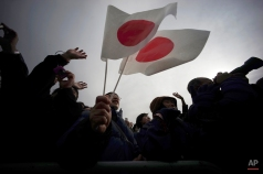Well-wishers wave Japanese flags to greet Japan's Emperor Akihito and Empress Michiko during New Year's public appearance of the imperial couple at the Imperial Palace in Tokyo, Friday, Jan. 2, 2015. (AP Photo/Eugene Hoshiko)